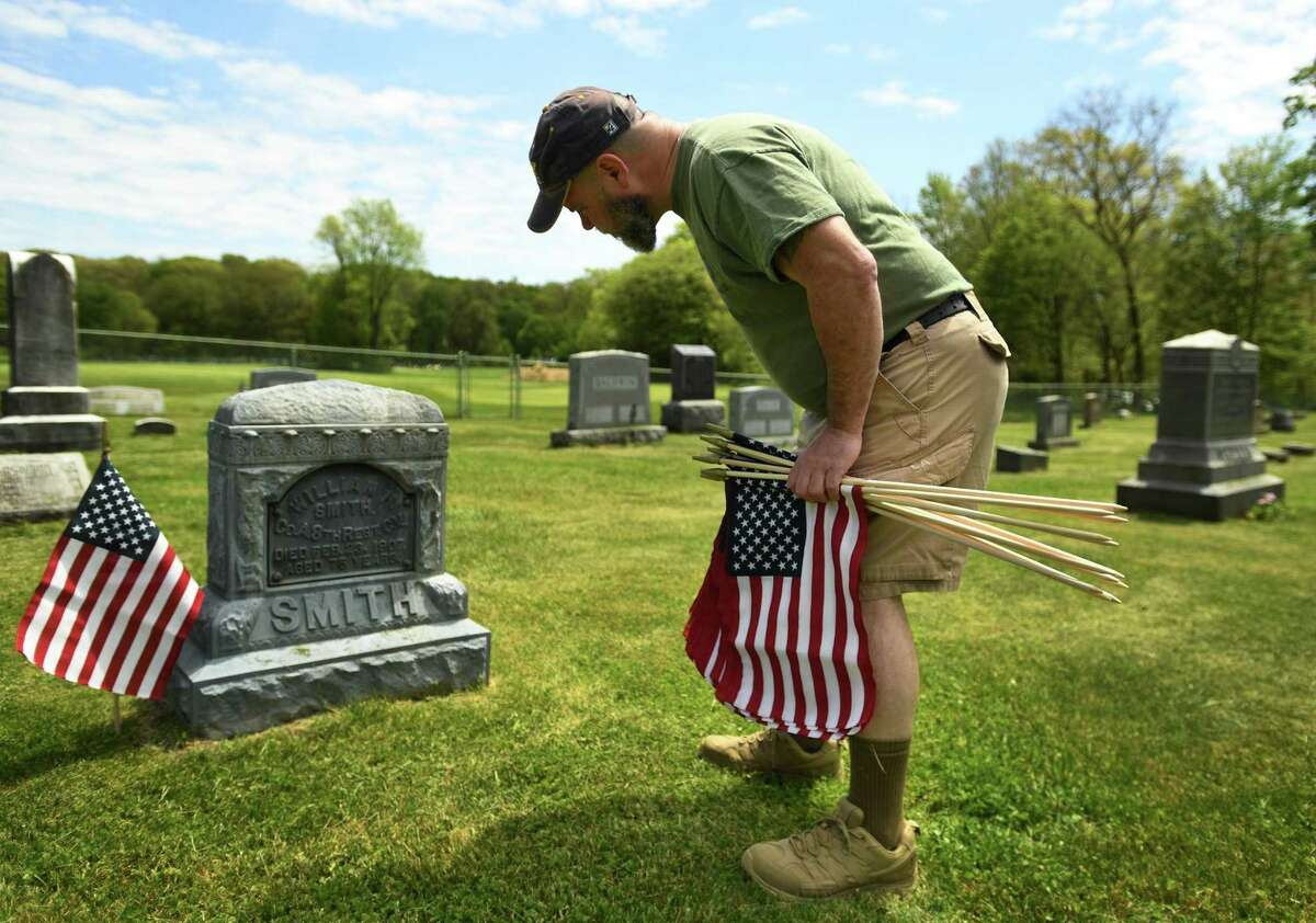 Mike Kellett, of Shelton, and fellow members of American Legion Post 16 place flags at the graves of military veterans at Lawn Cemetary in Shelton, Conn. on Sunday, May 17, 2020.