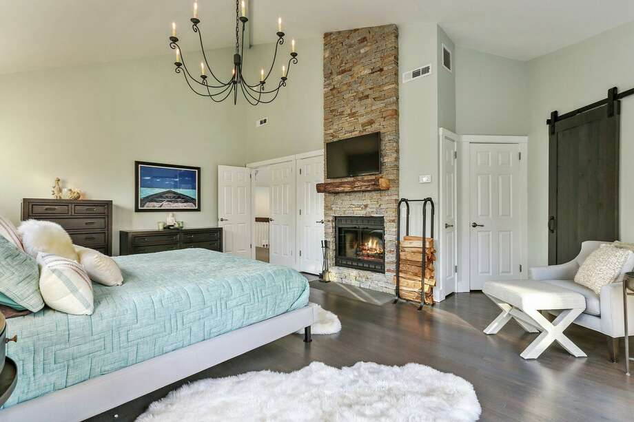 The master bedroom has a floor-to-ceiling stone fireplace, vaulted ceiling, sliding doors to a private balcony, and barn door to the master bath. Photo: Ree_ann_macachor