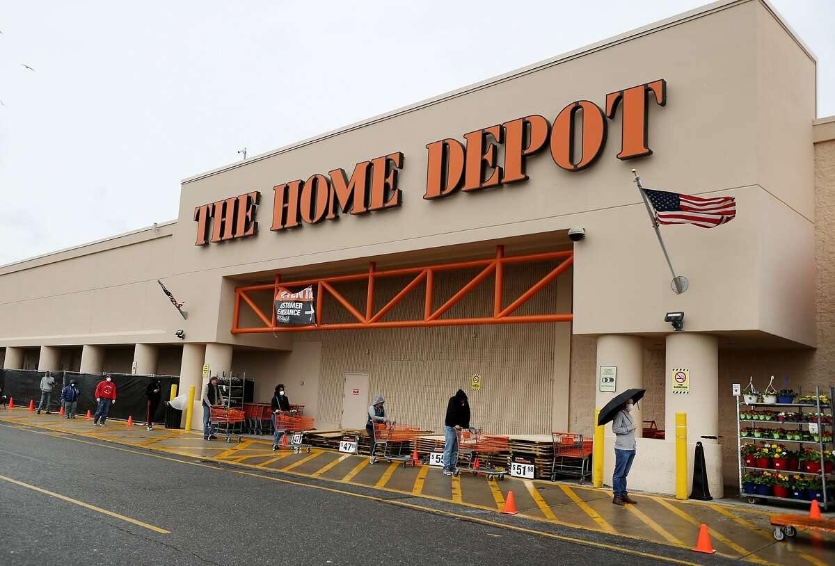 In this file photo, people wearing masks and gloves wait to enter Home Depot on April 03, 2020 in Freeport, New York. Due to the coronavirus (COVID-19) pandemic Home Depot implemented social distancing while shopping in the store by letting only a certain number of people enter at a time. Over the course of their first quarters, which run February to April, foot traffic at Home Depot rose 10% from a year ago, according to data from SafeGraph.