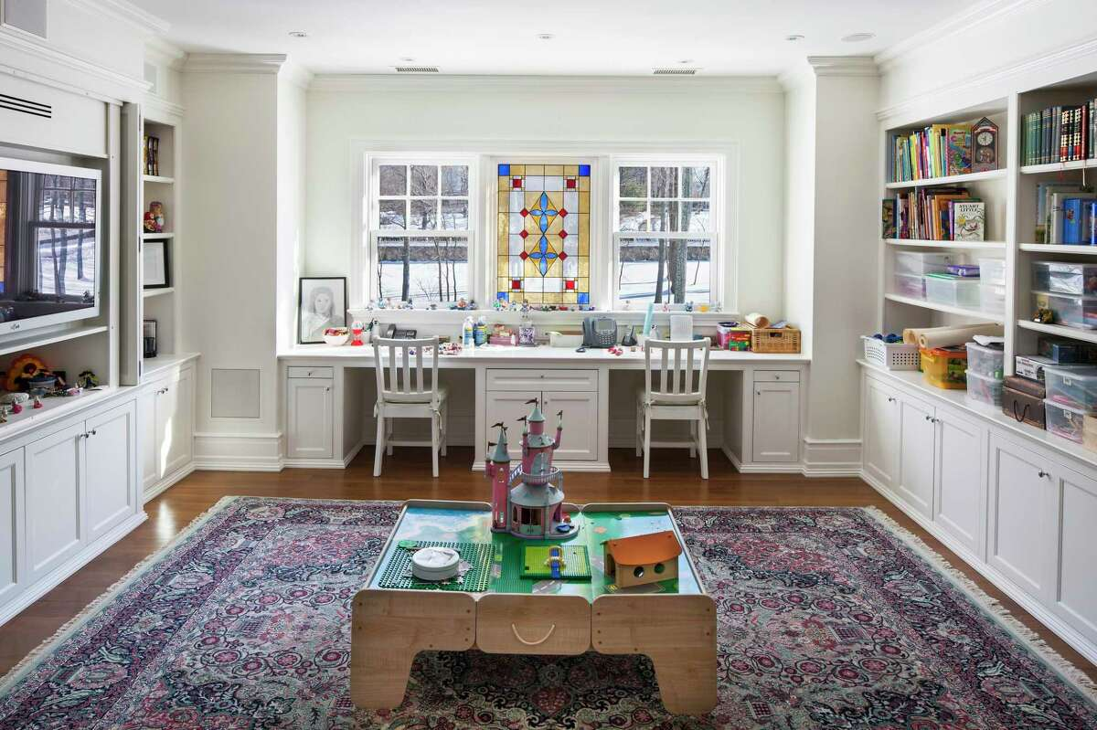 """A """"home office"""" for children has become a common request for architects, builders, and interior designers as children practice distance learning during the coronavirus. Here, a sunlit space, designed by Wadia Associates in New Canaan, features two desks and chairs, plenty of storage, bookshelves, and a gorgeous stained glass window, creating the perfect environment in which to work."""