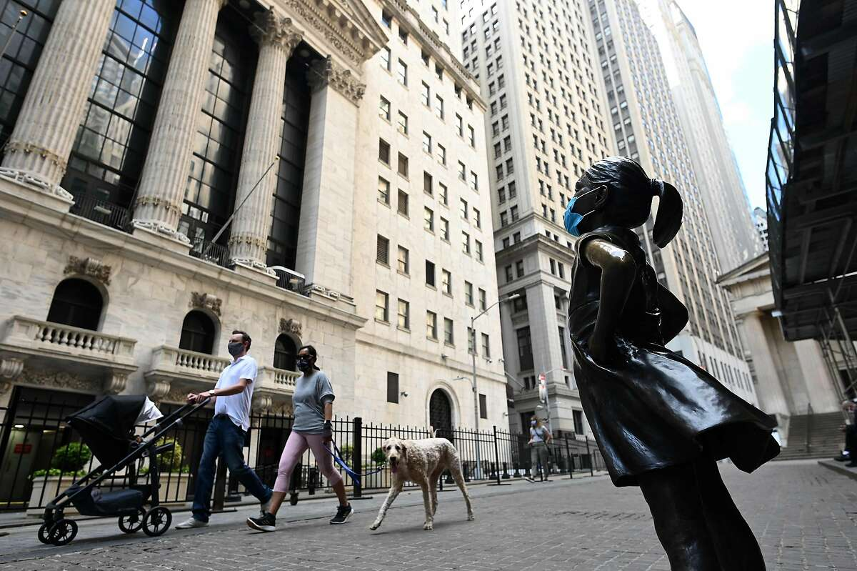 (FILES) In this file photo people walk by the masked bronze sculpture of the