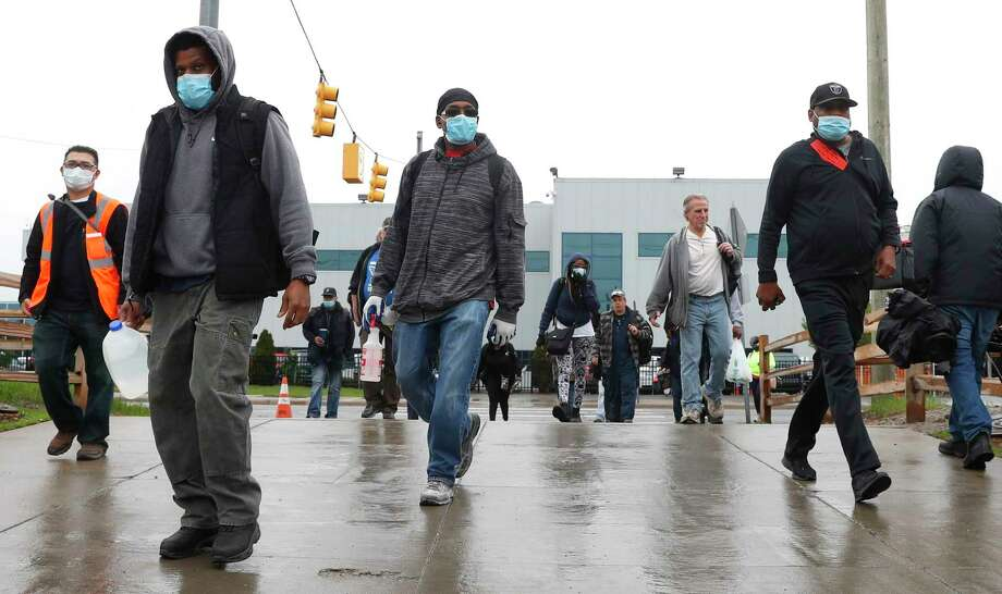 United Auto Workers members leave the Fiat Chrysler Automobiles Warren Truck Plant after the first work shift, Monday, May 18, 2020, in Warren, Mich. Fiat Chrysler Automobiles NV along with rivals Ford and General Motors Co., restarted the assembly lines on Monday after several week of inactivity due to the corona virus pandemic. (AP Photo/Paul Sancya) / Copyright 2020 The Associated Press. All rights reserved