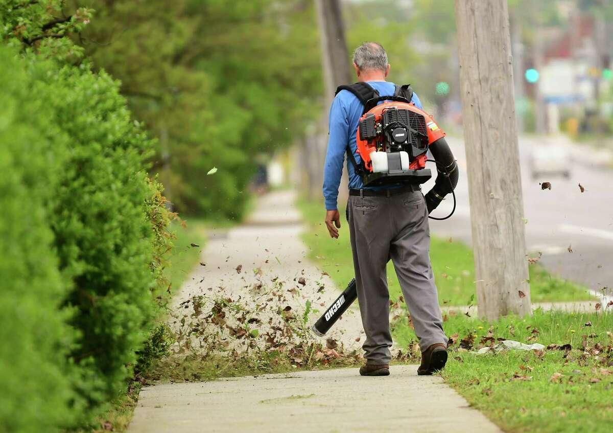 A man is seen blowing debris off a sidewalk along Western Ave. on Monday, May 18, 2020 in Albany, N.Y. (Lori Van Buren/Times Union)