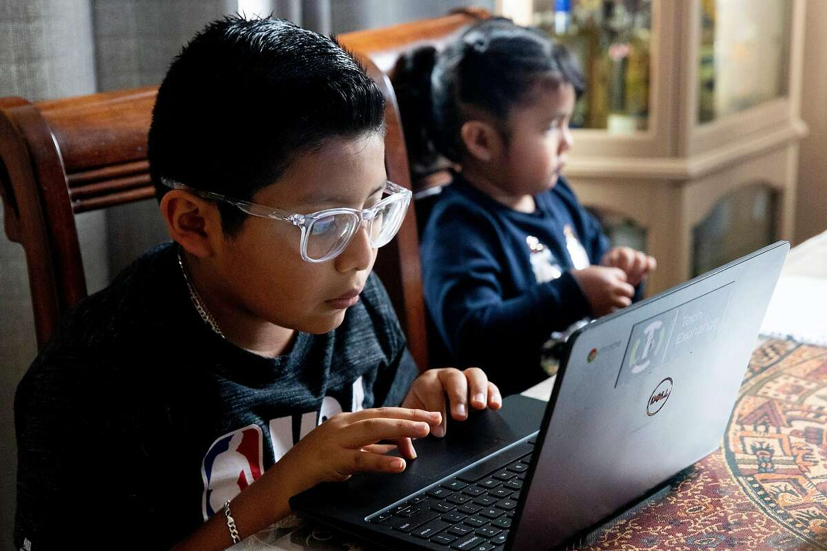 Edgar Porcayo-Perez Jr., 10, uses a communal laptop to do school work at their home in Oakland, Calif. Thursday, May 14, 2020.