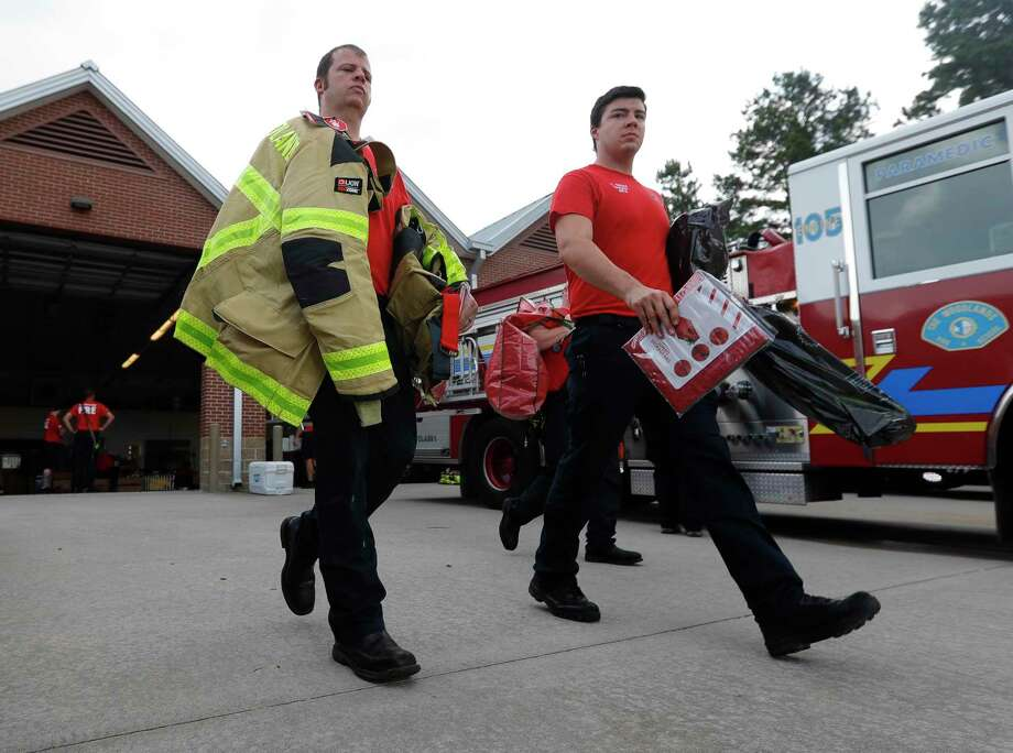 Chris Polnick, left, walks to his station's truck after he and other firefighters with The Woodlands Fire Department were issued new personal protective equipment, Friday, May 15, 2020, in The Woodlands. Thanks to a funding request being OK'd by township directors in 2019, the department was able to buy an entire second set of personal protective equipment for all 140 firefighters that is more modern and protects better against carcinogens. Photo: Jason Fochtman, Houston Chronicle / Staff Photographer / 2020 © Houston Chronicle
