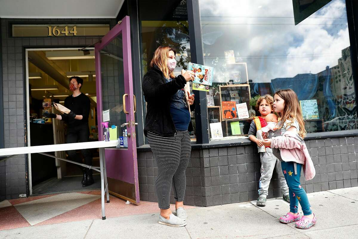 As The Booksmith's manager and buyer Camden Avery hands out an order, Amanda Rosen shows her 5-year-old twins, Sloane and Holden, books that she bought at the book store on Haight Street in San Francisco, Calif., on Monday, May 18, 2020. Retail stores in San Francisco and other Bay Area counties are now permitted to sell inventory curbside.