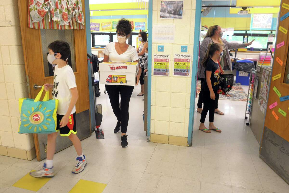 Students and parents leave classrooms with their personal belongings at Sunnyside School, in Shelton, Conn. May 18, 2020. Shelton elementary schools were opened Monday so students could retrieve their personal belonging.