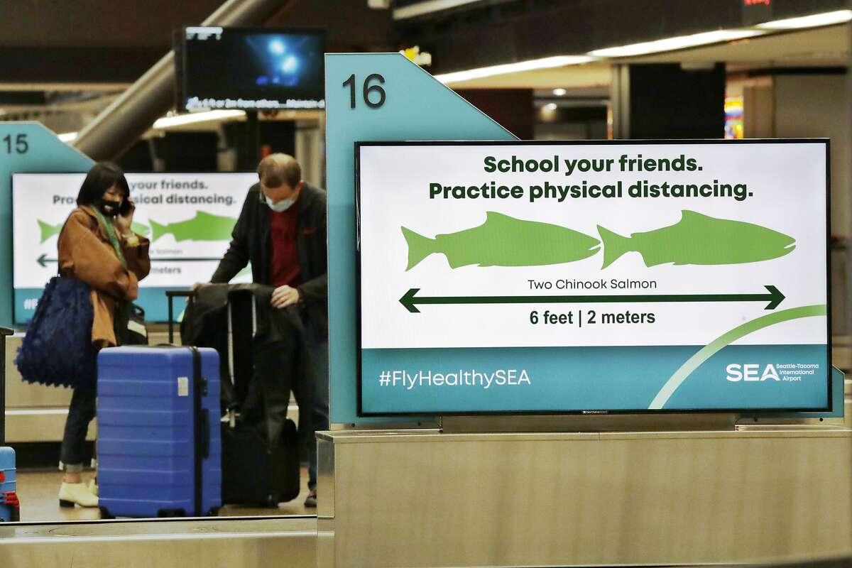 Travelers pick up luggage where signs remind them, with classic Pacific Northwest icons showing the size of two Chinook salmon, to stay six feet apart at Seattle-Tacoma International Airport Monday, May 18, 2020, in SeaTac, Wash.