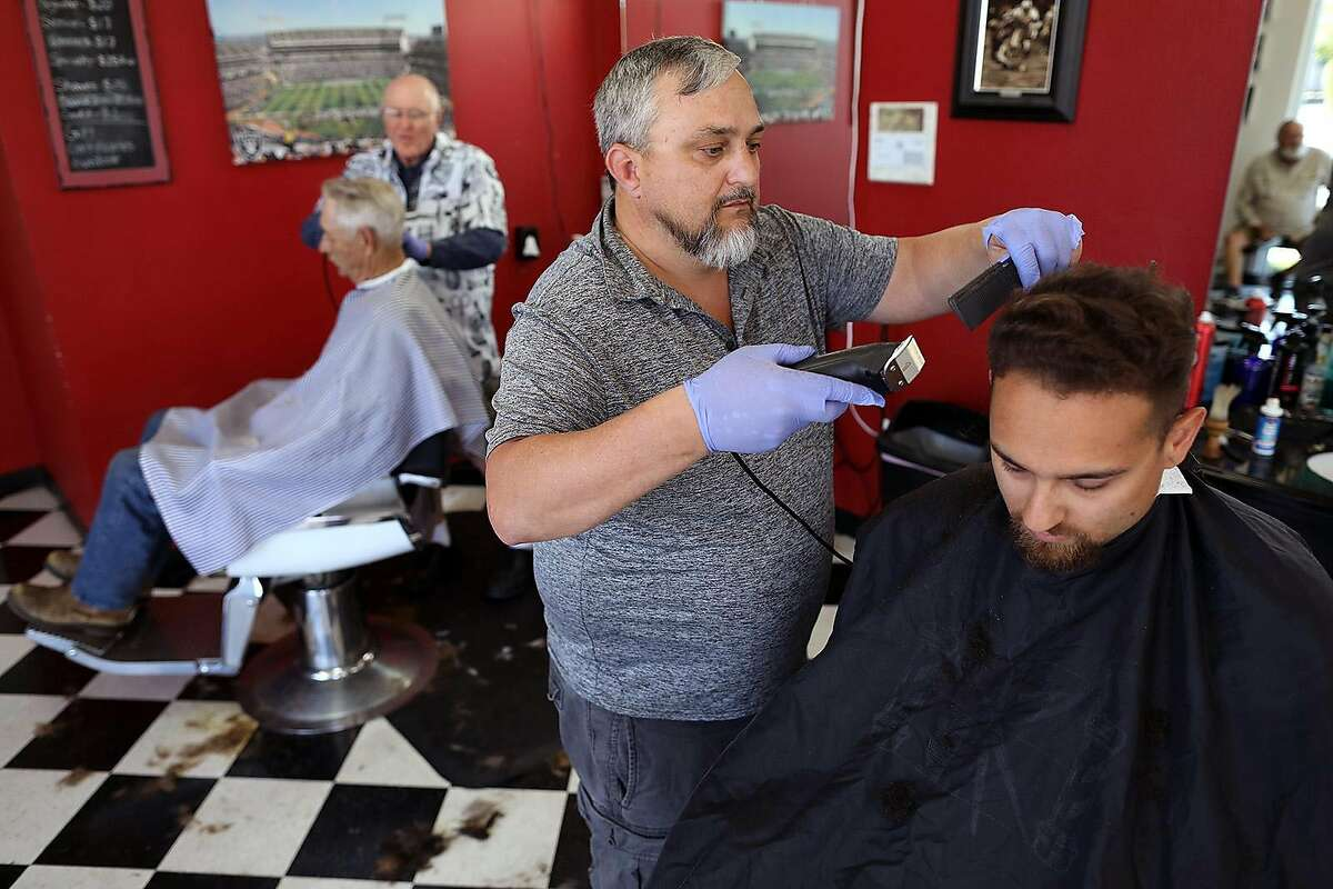 Wes Heryford, center, owner, who has been cutting hair for over 24-years, works on Ben Martin, 25, at Butte House Barber Shop on Wednesday, May 6, 2020, in Yuba City, Calif. Heryford closed his business on March 22 due to the coronavirus and opened back up on May 5. (Gary Coronado/Los Angeles Times/TNS)