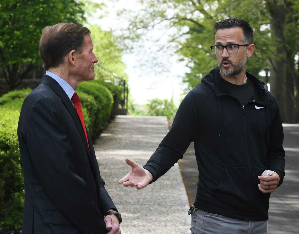 The Rev. Patrick Collins, right, and U.S. Sen.. Richard Blumenthal, D-Conn., speak at First Congregational Church of Greenwich last May. Collins put flags in front of the church to mark the number of COVID deaths in Connecticut. That number has now exceeded 500,000 nationwide.