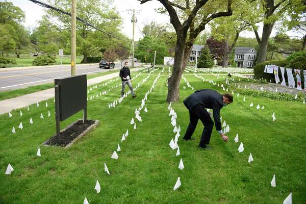 The Rev. Patrick Collins, left, and U.S. Sen.. Richard Blumenthal, D-Conn., place flags in memory of the Connecticut lives lost from coronavirus at First Congregational Church of Greenwich last May.