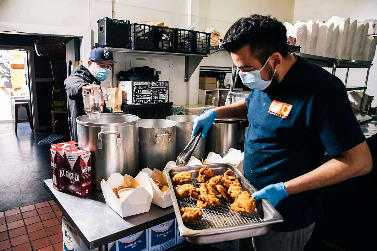 Christian Ciscle, chef-owner of SF Chickenbox, left, prepares a pickle brine as Pedro Giron distributes fried chicken into to-go boxes at SF Chickenbox in San Francisco, Calif. on Friday, May 15, 2020.