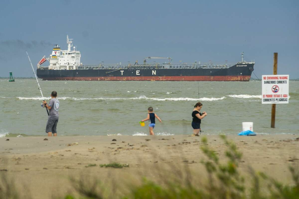 An oil tanker sits offshore between Galveston Bay and the Gulf of Mexico where people fish and enjoy the beach, Friday, May 15, 2020, on the east end of Galveston Island.