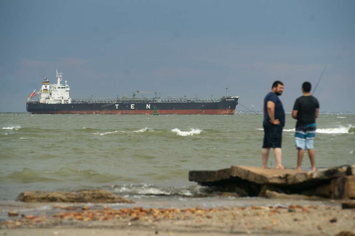 An oil tanker sits offshore between Galveston Bay and the Gulf of Mexico near people fishing, Friday, May 15, 2020, off of the east end of Galveston Island.