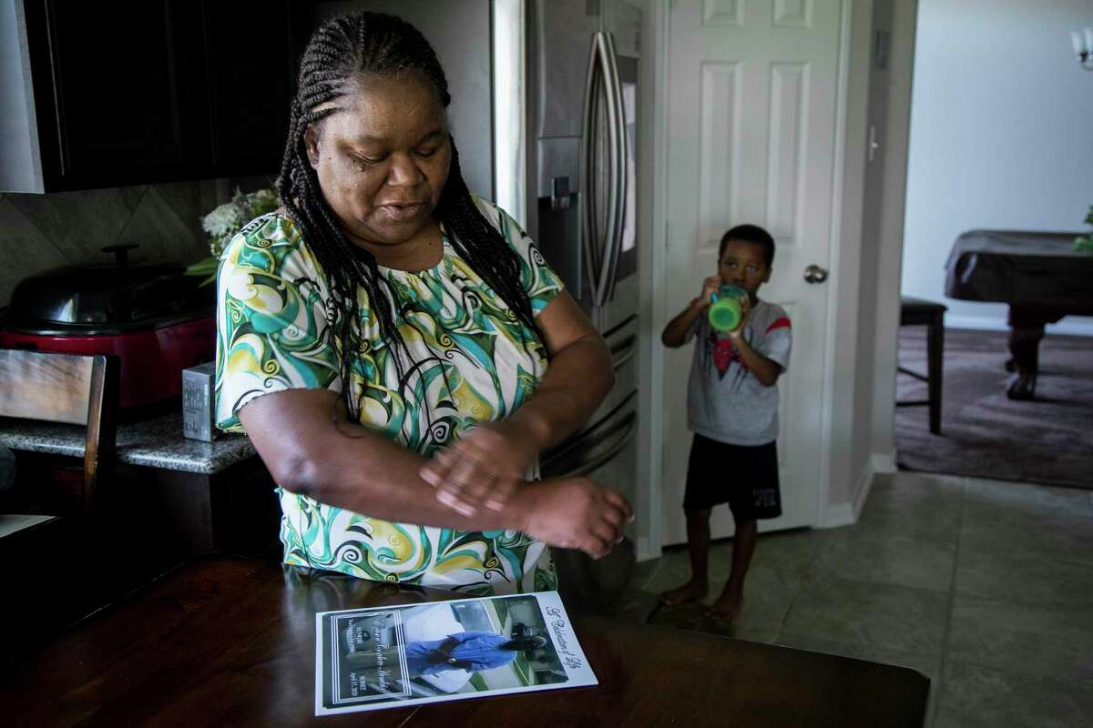 """Shelia Hendrix stands with her grandson, Tyree Heath, in her kitchen looking at a photo of her son, Edison """"Tater"""" Hendrix, 33, on Thursday, May 7, 2020, in Houston. Hendrix remembers her son, whom she nicknamed """"Tater"""" as a baby, as a big-hearted truck driver who loved getting behind the wheel of his 2011 Chevy Camaro in his free time. After he followed his father into the trucking industry, he persuaded friends to join him to get them off the street."""