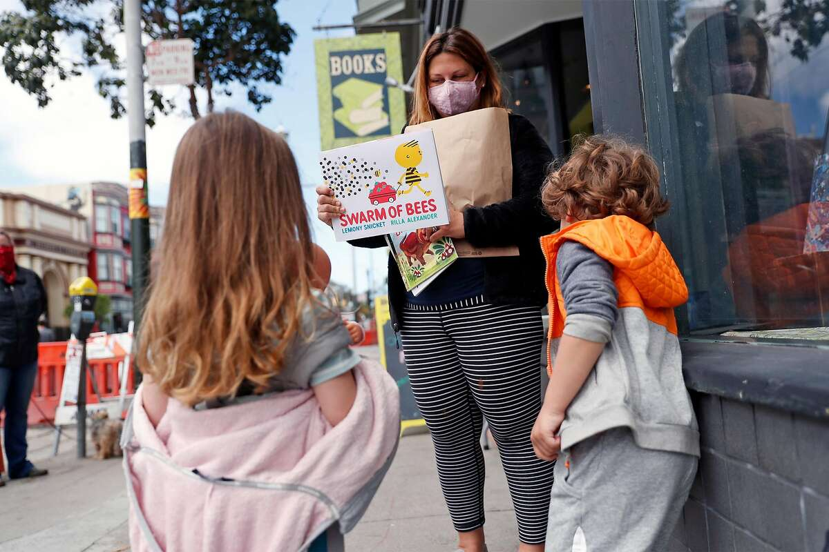 Amanda Rosen shows her 5-year-old twins, Sloane and Holden, books that she bought at The Booksmith on Haight Street in San Francisco, Calif., on Monday, May 18, 2020. Retail stores in San Francisco and other Bay Area counties are now permitted to sell inventory curbside.