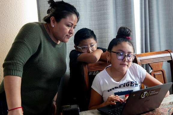 In this file photo, Oakland mother Jacqueline Perez-Rosales is checking the homework of Edgar Porcayo-Perez Jr., 10, before her daughter Montse Porcayo-Perez, 11, takes her turn on the communal laptop Jacqueline received from a nonprofit organization. The COVID-19 pandemic has uncovered not just one, but three digital divides when it comes to student learning.