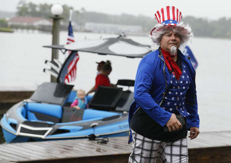 Chad Myers, dressed as Uncle Sam, fights back heavy wind and light rain as he and other supporters of President Donald Trump gathered on Lake Conroe for a boat parade, Saturday, May 16, 2020, in Conroe. Photo: Jason Fochtman/Staff Photographer / 2020 ? Houston Chronicle