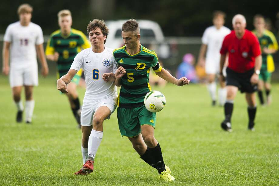 Dow High's Tyler Lyman (right) battles Midland High's Aidan Wilber-Gauthier for the ball during a Sept. 25, 2019 match. Dow's current grass soccer field will be replaced by a new artificial turf field in the months ahead. Photo: Daily News File Photo