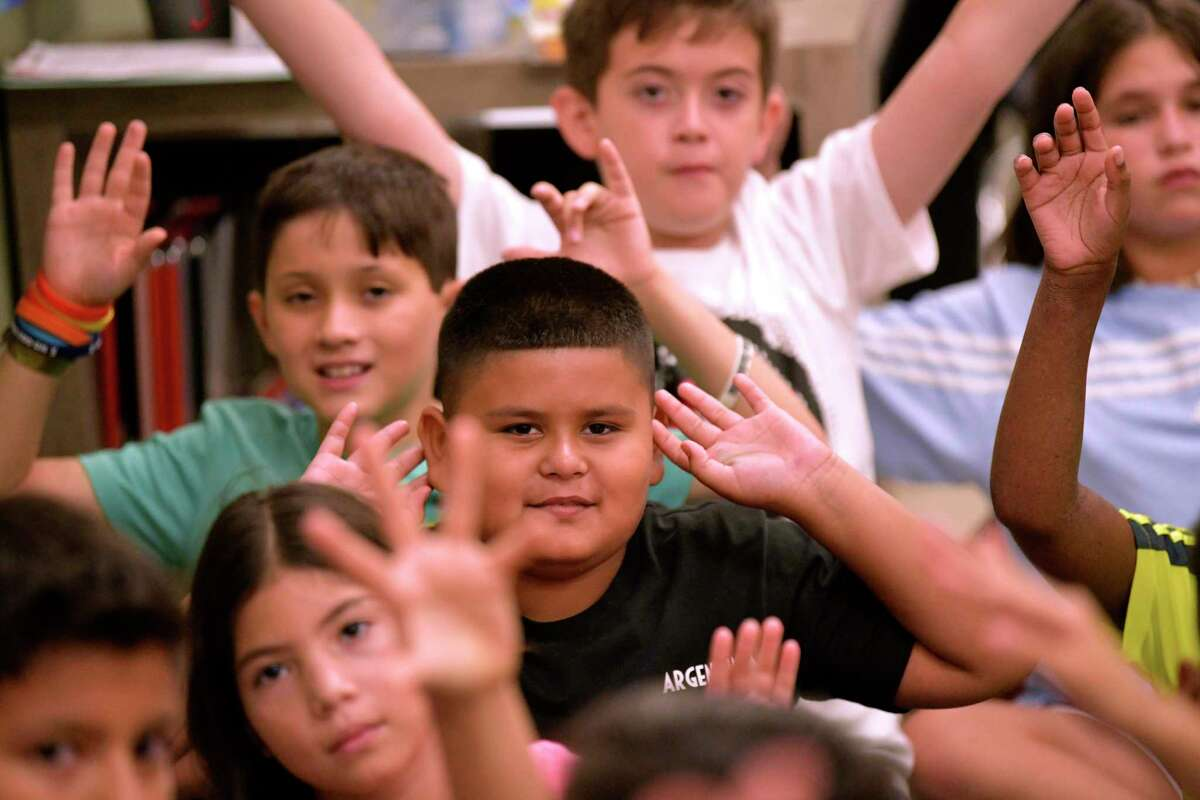 Luis Fabela, middle, and his fifth grade classroom at Ellison Elementary raise their hands during class in 2019. San Antonio's larger school districts are planning to offer a return to in-person classes this summer.