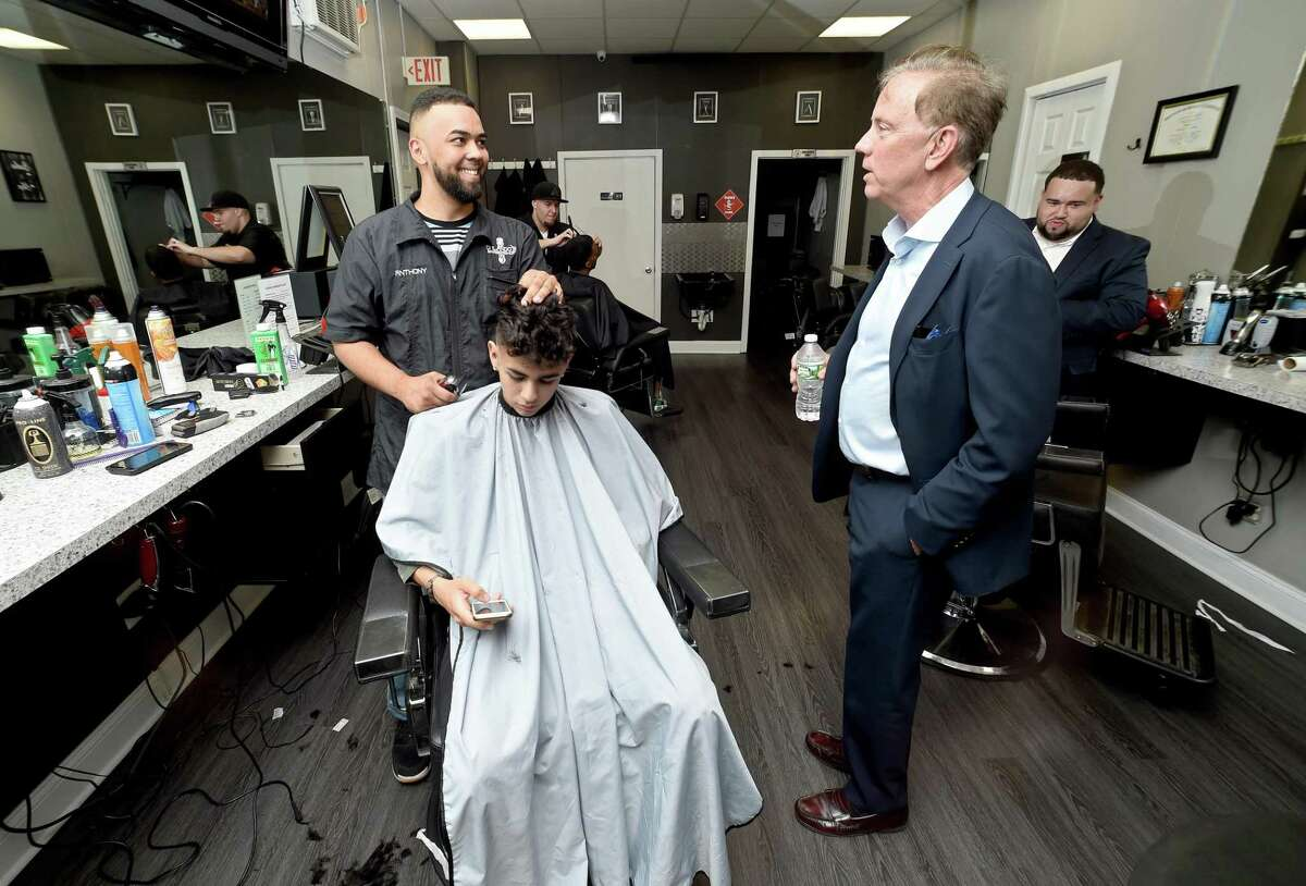 Then-candidate, now-Gov. Ned Lamont talks with Anthony Rivera (left) while Rivera cuts the hair of Alejandro Sanchez of East Haven at Orlando's Barber Shop on Grand Avenue in Fair Haven in 2018. On Monday, Lamont delayed the reopening of hair salons and barbershops to June 1, just two days before the scheduled restart.