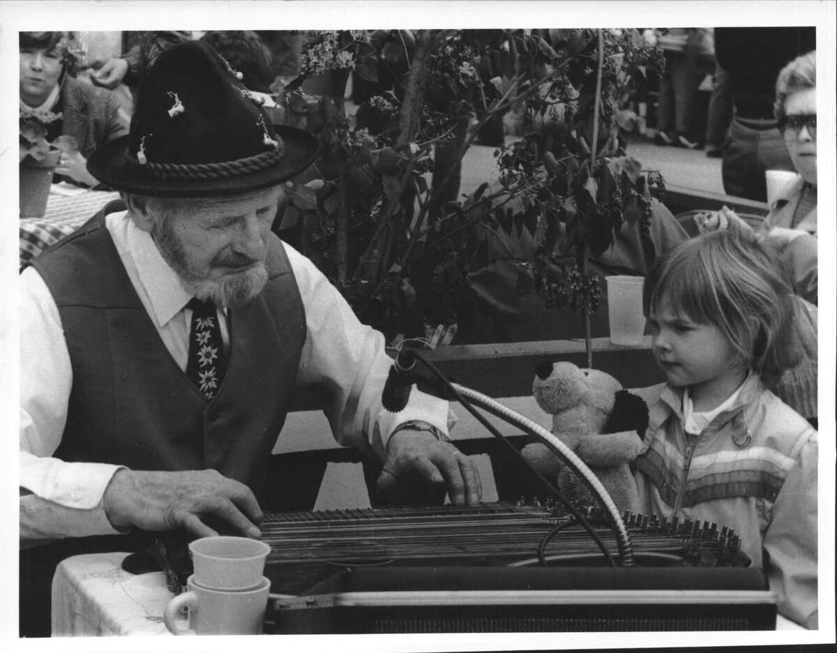 Schenectady Museum, New York - Festival of Nations - Fritz C. Lausen of Schenectady, playing a German zither, and Heather A. Farry, 4-year-old daughter of Mr. and Mrs. Jack Farry of Niskayuna, at the German booth. May 19, 1984 (Bob Richey/Times Union Archive)