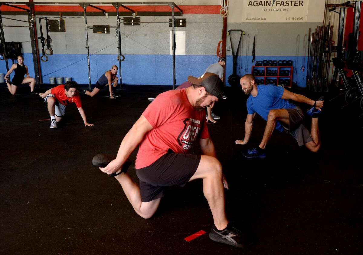 Gym owner Jason Wilkins (right) leads a series of opening stretches during a class at NorBeau CrossFit Monday, the first day gyms and fitness centers were allowed to reopen throughout Texas. Photo taken Monday, May 18, 2020 Kim Brent/The Enterprise