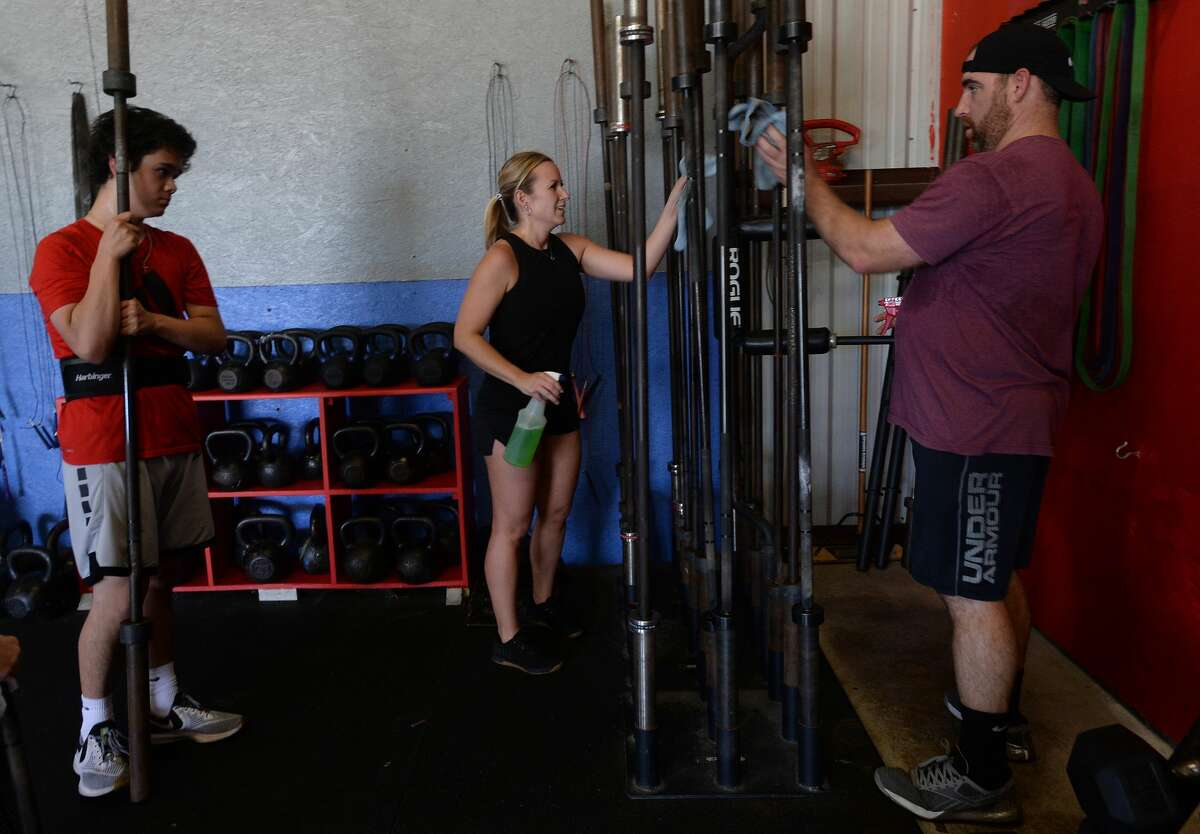 Barbels are wiped down after use during a class at NorBeau CrossFit Monday, the first day gyms and fitness centers were allowed to reopen throughout Texas. Photo taken Monday, May 18, 2020 Kim Brent/The Enterprise