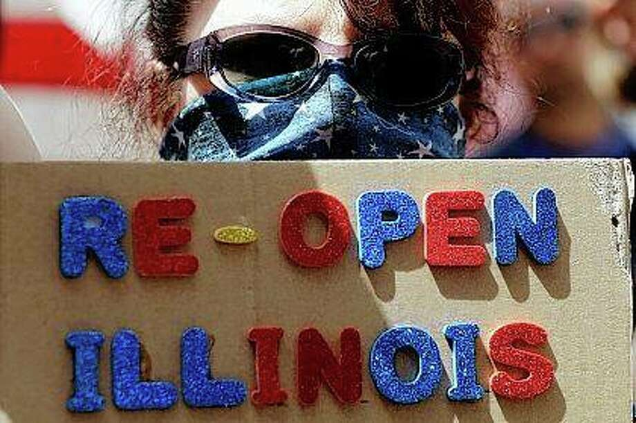 A protester holds a sign Saturday during a rally outside the Thompson Center in downtown Chicago calling for the state to reopen the economy. Illinois Republicans want a General Assembly vote on removing from the fall ballot Gov. J.B. Pritzker's proposed graduated income tax structure, saying the state's pandemic-pillaged economy can't sustain higher taxes. Photo: Nam Y. Huh