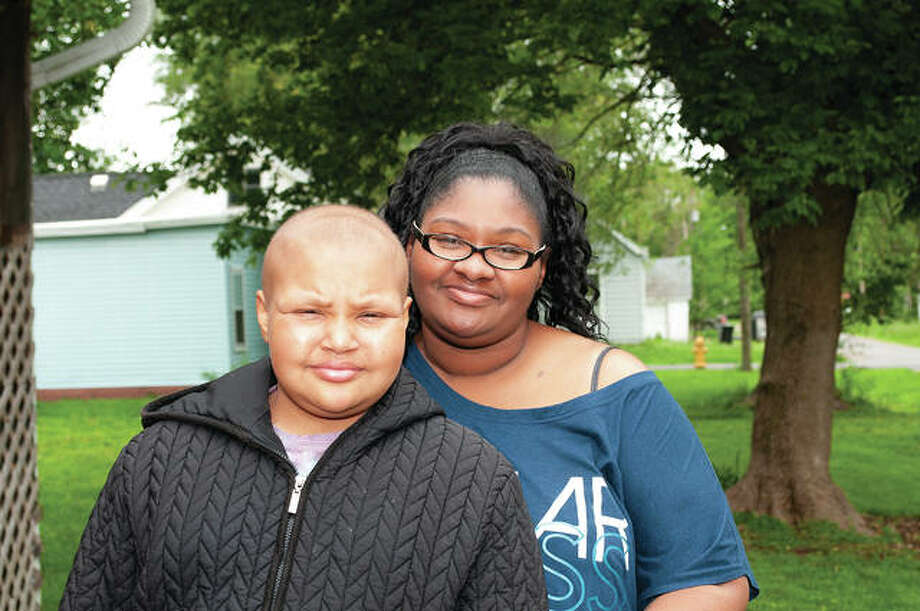 Darkena Burton (left), 11, won her fight against cancer and got to ring a bell indicating her triumph. Darkena's mother, Ida Burton, said the girl had osteosarcoma — a common type of cancer that arises in bones — and received a new right femur and a reconstructed knee. Darkena also went through 18 rounds of chemotherapy. Photo: Darren Iozia | Journal-Courier