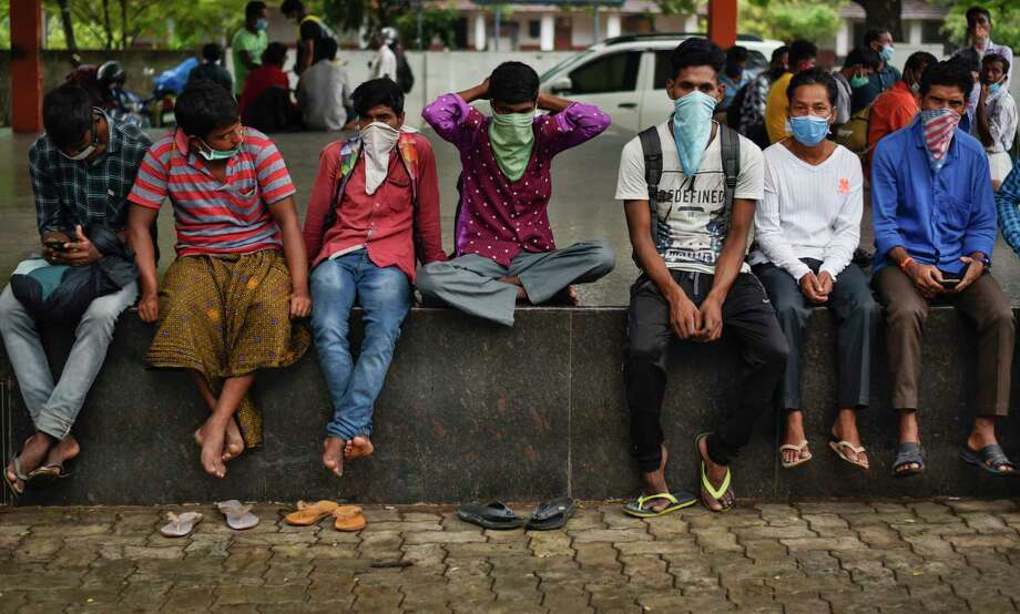Migrant workers who have yet been unable to return to their home states in north India sit wearing masks at a town square during lockdown in Kochi, In the southern Indian state of Kerala, Tuesday, May 19, 2020. The number of coronavirus cases in India has surged past 100,000,  with most of the cases being in major cities. But rural villages across India are also seeing an increase in cases with the return of hundreds of thousands of migrant workers who left cities and towns where they were abandoned by their employers after having toiled for years building homes and roads. Photo: R S Iyer, AP / AP