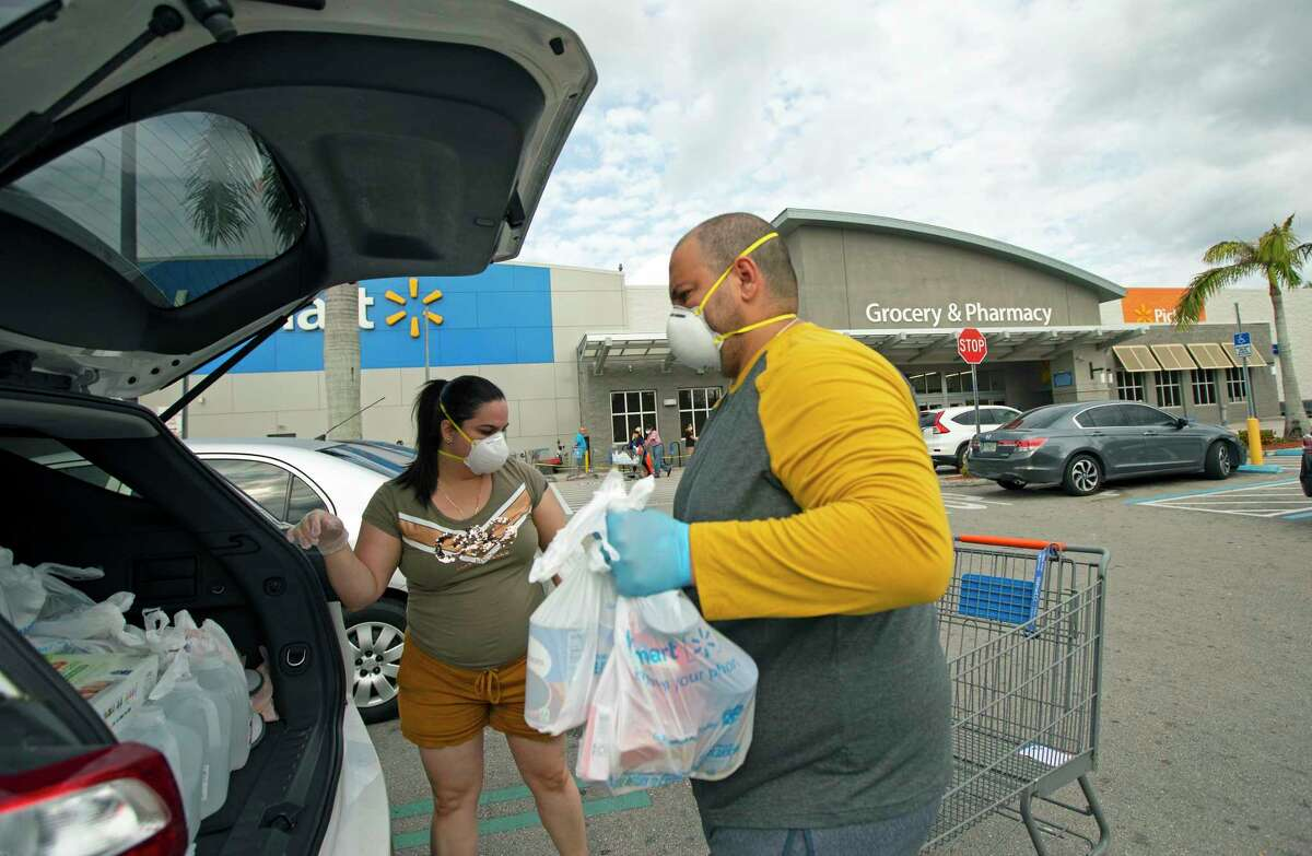 FILE - In this Sunday, April 5, 2020 file photo, Joel Porro and Lizz Hernandez wear gloves and protective masks as they put bags in the trunk of their car after shopping at Walmart Supercenter in Miami. On Friday, April 10, 2020, The Associated Press reported on stories circulating online incorrectly asserting that due to the COVID-19 pandemic, effective immediately, Walmart is adopting a staggered shopping schedule based on age. Walmart is offering special hours for seniors but has not designated times for people to shop by age group. (David Santiago/Miami Herald via AP)