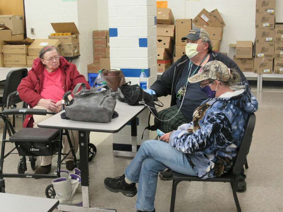 Left to right, Lorraine Petersen, Jon St. Croix and Sharon St. Croix sit in the shelter space set up in the cafeteria of Meridian Jr. High School after being evacuate from their homes on Wixom Lake on May 19, 2020. Photo: Mitchell Kukulka