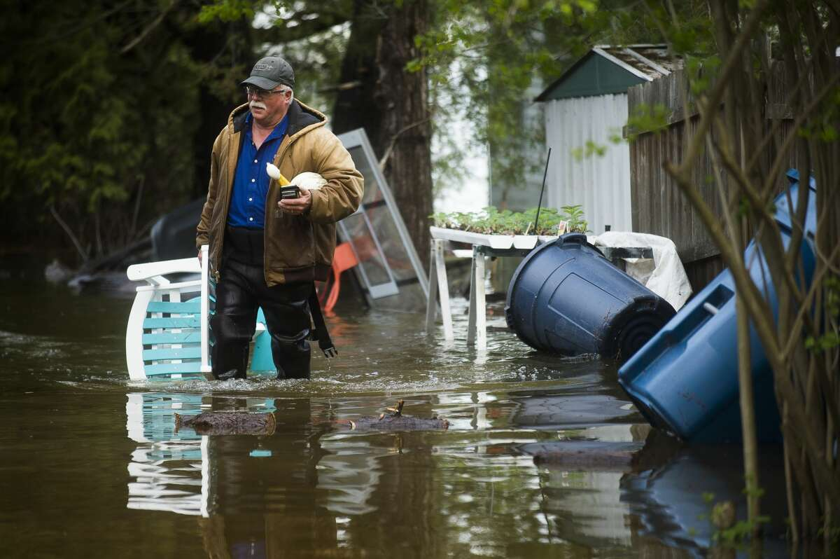Mark Musselman brings a chair to the front of his house from the back yard, wading through floodwater, Tuesday, May 19, 2020. An evacuation order was released the night before for residents of Sanford and Wixom Lakes, warning of