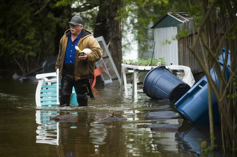 "Mark Musselman brings a chair to the front of his house from the back yard, wading through floodwater, Tuesday, May 19, 2020. An evacuation order was released the night before for residents of Sanford and Wixom Lakes, warning of ""imminent dam failure."" ""We're all safe, that's the main thing,"" said Mark's wife, Ruth Musselman. (Katy Kildee/kkildee@mdn.net) Photo: (Katy Kildee/kkildee@mdn.net)"