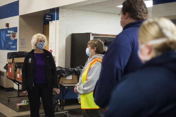 """State Rep. Annette Glenn speaks with volunteers at an emergency shelter at Meridian Junior High for residents of Sanford and Wixom Lakes Tuesday, May 19, 2020 after an evacuation order the night before warning of """"imminent dam failure."""" (Katy Kildee/kkildee@mdn.net)"""