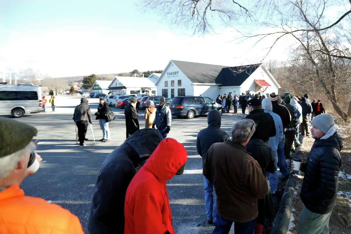Customers wait on line in the cold on the opening day of recreational marijuana sales at Theory Wellness in Great Barrington, Mass., Friday, January 11, 2019. Theory is the first dispensary in the Berkshires to open its doors for recreational marijuana sales and the opening makes Theory the 6th dispensary of its kind in the state. (Stephanie Zollshan/The Berkshire Eagle via AP)