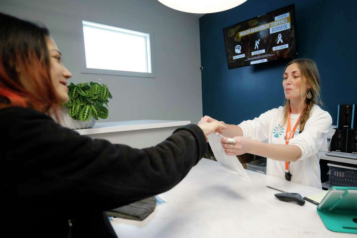 Mary Starsja, left, makes her first purchase from Megan Wendling-Kane on opening day for recreational marijuana sales at Temescal Wellness, Tuesday, Jan. 15, 2019, in Pittsfield, Mass. (Stephanie Zollshan/The Berkshire Eagle via AP)