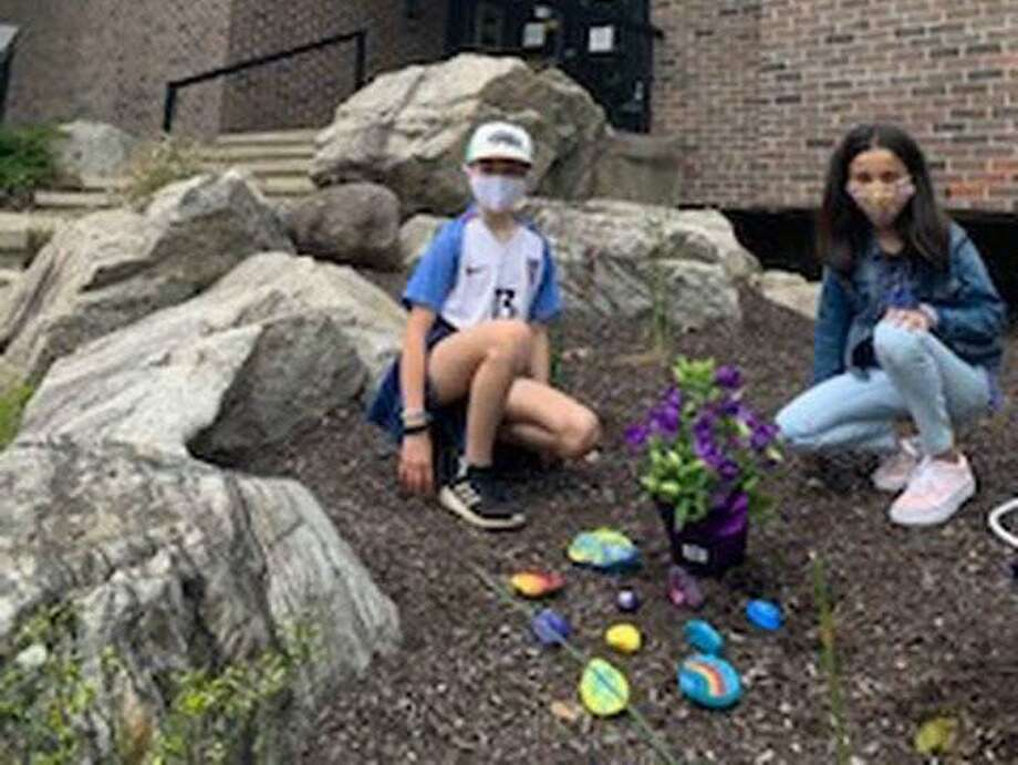 Two fourth graders from Cider Mill School placed hand-painted rocks with inspirational messages and flowers outside Wilton Police, Fire and WVAC headquarters. Photo: Contributed Photo