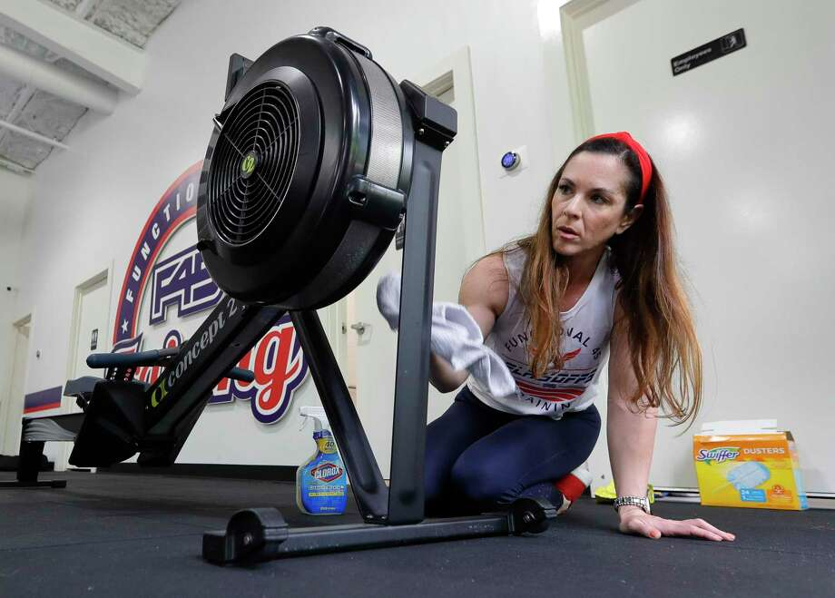 Co-owner Jodi Tompkins sanitizes equipment at F45 Training, Saturday, May 16, 2020, in Montgomery. Gyms reopened Monday at 25 percent capacity as part of Gov. Greg Abbott's phased reopening of the Texas economy. Photo: Jason Fochtman, Houston Chronicle / Staff Photographer / 2020 © Houston Chronicle