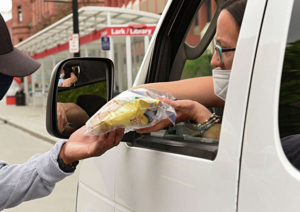 Associate Director of Outreach Tiana Minervini, right, hands a bag of food to a homeless man as the Albany Outreach Van drives around and delivers food for the homeless on Monday, May 18, 2020 in Albany, N.Y. The program has seen the unsheltered triple due to fears of contracting the virus in a shelter. (Lori Van Buren/Times Union)