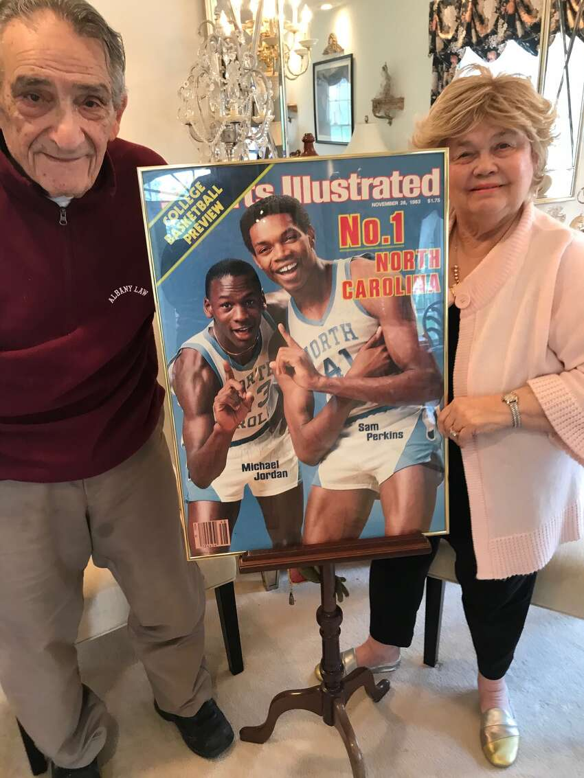 ohn and Marlene Elacqua pose with the Sports Illustrated cover signed by Michael Jordan and Sam Perkins, who lived with the Elacquas his senior year at Shaker High School in 1979-80.