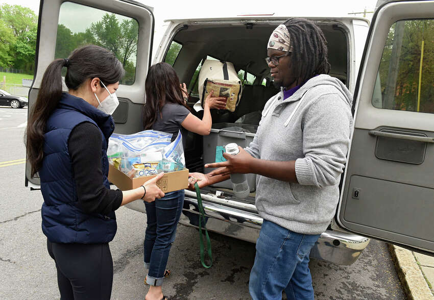 Volunteer Kikari Morikawa, left, Joseph's House Associate Director of Outreach Tiana Minervini, center, and Joseph's House Outreach Advocate Ptah Ivery load the Albany Outreach Van on Monday, May 18, 2020 in Albany, N.Y. The Homeless Action Committee drove around the city and delivered food, water and supplies to people in need. The program has seen the unsheltered triple due to fears of contracting the virus in a shelter. (Lori Van Buren/Times Union)