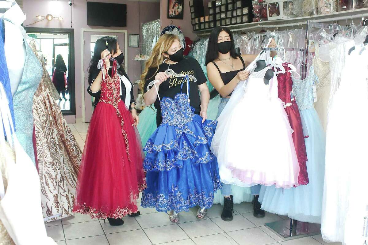 Katherine Dugan, Andrea's Bridal owner Nancy Ornelas and Valeria Romualdo examine girls' formal and quinceanera style dresses in their Pasadena shop Thursday, May 7.