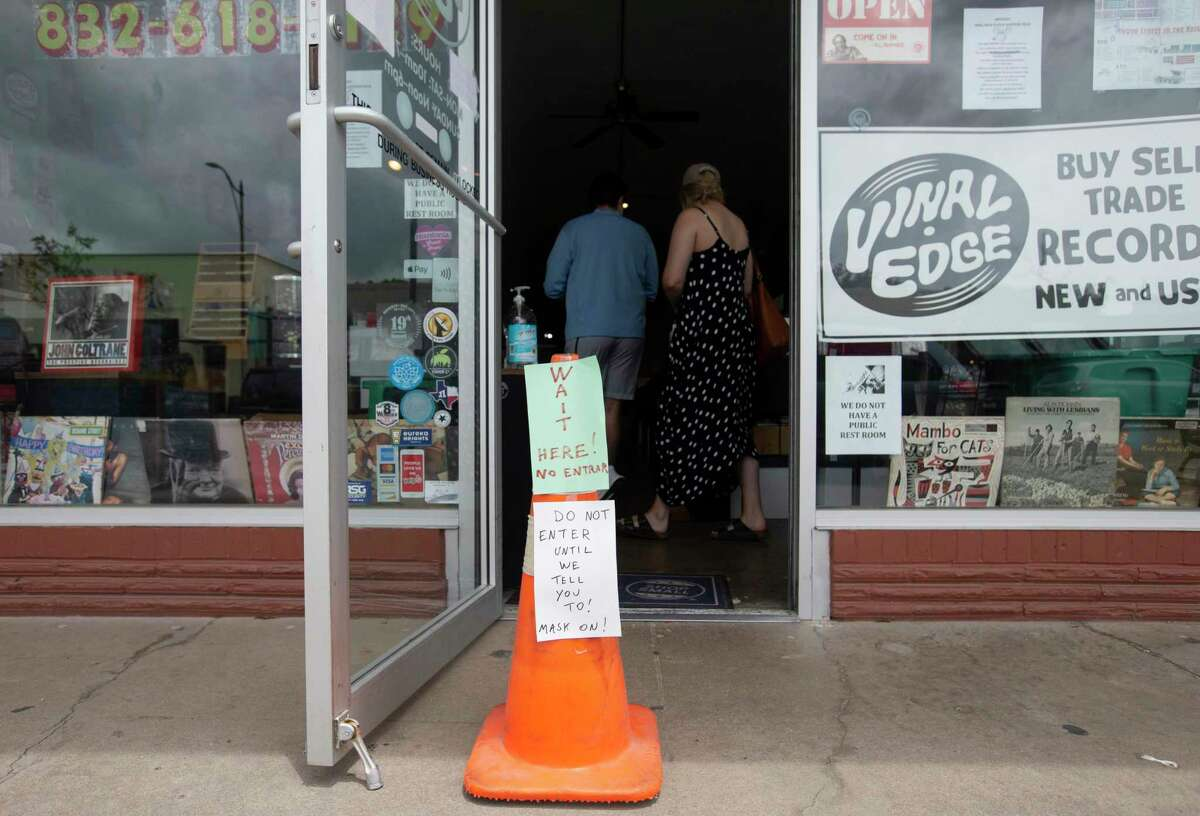 Vinal Edge Records puts out new store protocols during the coronavirus outbreak Thursday, May 14, 2020, at the Heights in Houston. The record shop has been limiting four guests inside the shop, using hand sanitizer once they walk in and requiring them to wear a face cover.