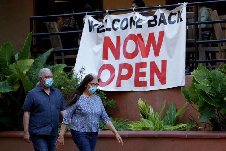 Visitors to the River Walk pass a restaurant that has reopened in San Antonio, Monday, May 18, 2020. Texas Gov. Greg Abbott announced Monday that bars and bowling alleys are on the list of business that can reopen at 25 percent beginning Friday and restaurants can increase to 50 percent capacity as the state continues to go through phases to reopen the state after closing many businesses to battle the spread of the coronavirus. (AP Photo/Eric Gay)