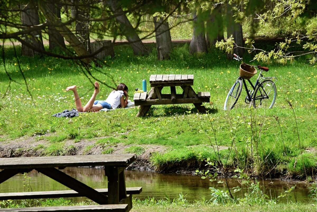 Leah Clifford of Saratoga Springs takes a break from biking to read by the stream in Saratoga Spa State Park on Tuesday, May 19, 2020 in Saratoga Springs, N.Y. (Lori Van Buren/Times Union)