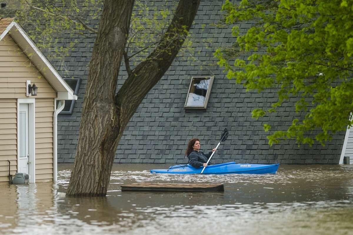 People use kayaks to assess the damage at homes in their neighborhood on Oakridge Road on Wixom Lake Tuesday, May 19, 2020 in Beaverton. (Katy Kildee/kkildee@mdn.net)