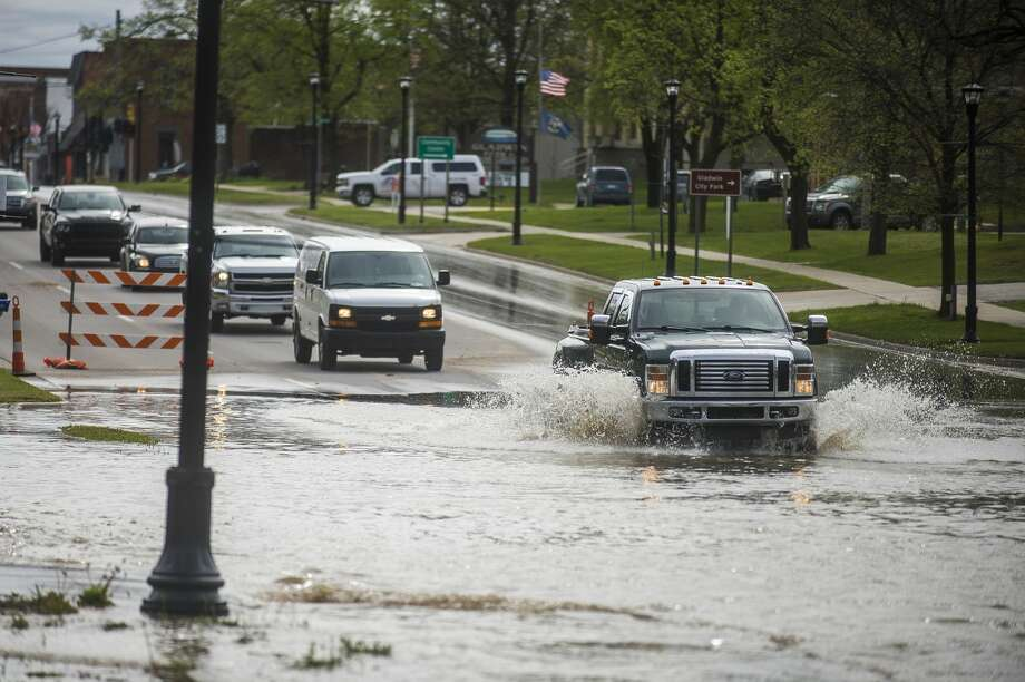 Vehicles drive through floodwater in downtown Gladwin Tuesday, May 19, 2020. (Katy Kildee/kkildee@mdn.net) Photo: (Katy Kildee/kkildee@mdn.net)