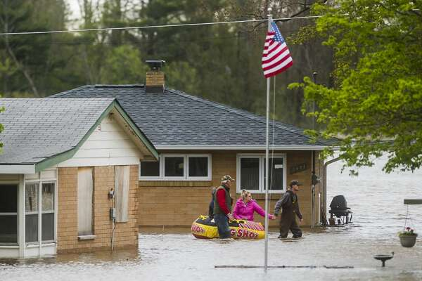 People help each other travel from one home to another using an inflatable raft on Oakridge Road on Wixom Lake Tuesday, May 19, 2020 in Beaverton. (Katy Kildee/kkildee@mdn.net)